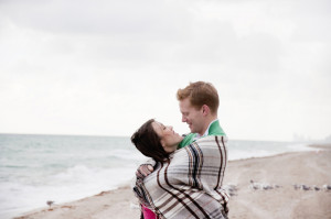 couple wrapped in blanket on beach