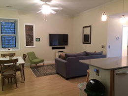livingroom with grey couch, green side chair wall mounted TV and white ceiling fan.