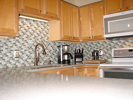 Kitchen with tan cabinets, grey counter tops, blue/grey patterened backsplash.