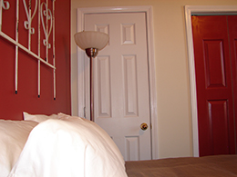 side view of a queen bed with white pillows and stainless steel floor lamp and white door.