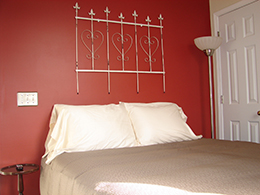 Queen bed with tan duvet and white pillows against a rich red wall.