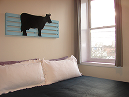 King bed with white pillows and wall art of a blue fence and black cow.