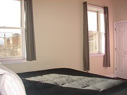 king bed with white pillows and sunlight hitting the bed from two windows with grey curtains.