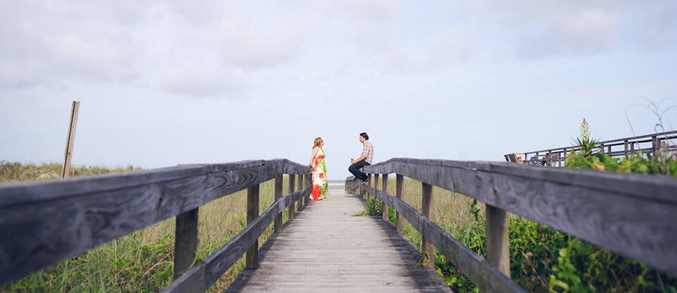Heather in long flowing dress with red and green print across from Mike sitting on the wooden walkway to the beach