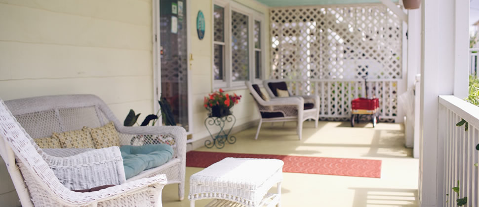 front porch of the inn with white whicker furniture, yellow siding, light blue ceiling and red wagon in the background
