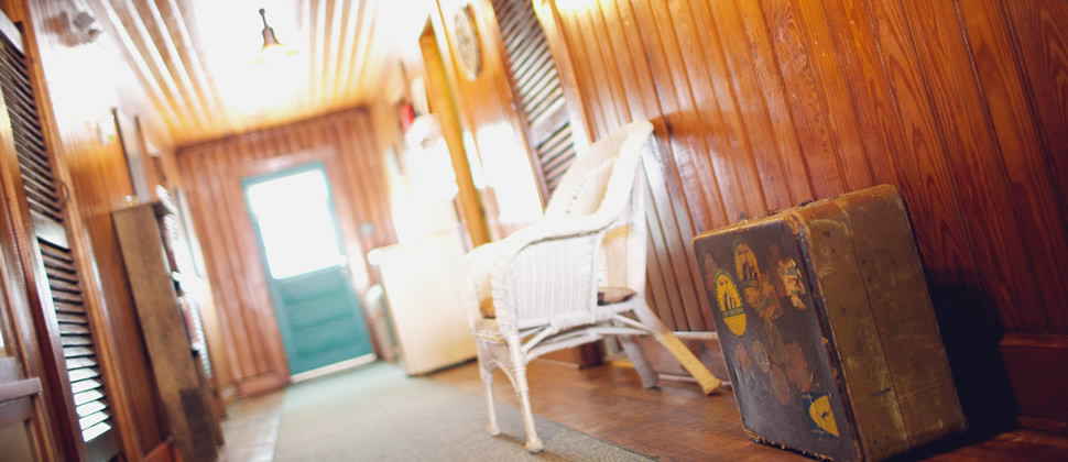 Upstairs hallway of the Inn with a vintage brown suitcase and white chair