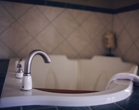 close up of our whirlpool Jacuzzi tub with a white bathmat draped over the tub and shinny nickel platted facet