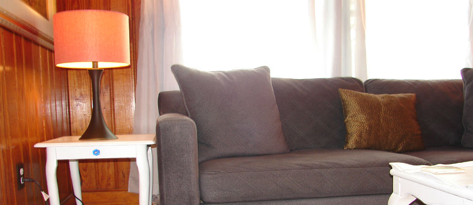 living room, blue/grey couch in front of two windows, white end table with illuminated brown lamp and orange shade.