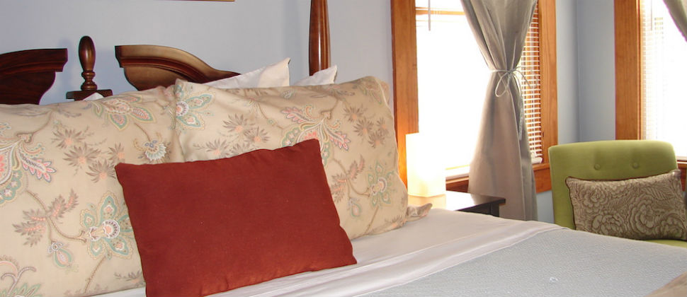 Beacon's 9 on the first floor queen bed with a red throw pillow leaning against brown shams and a green chair in backgound.