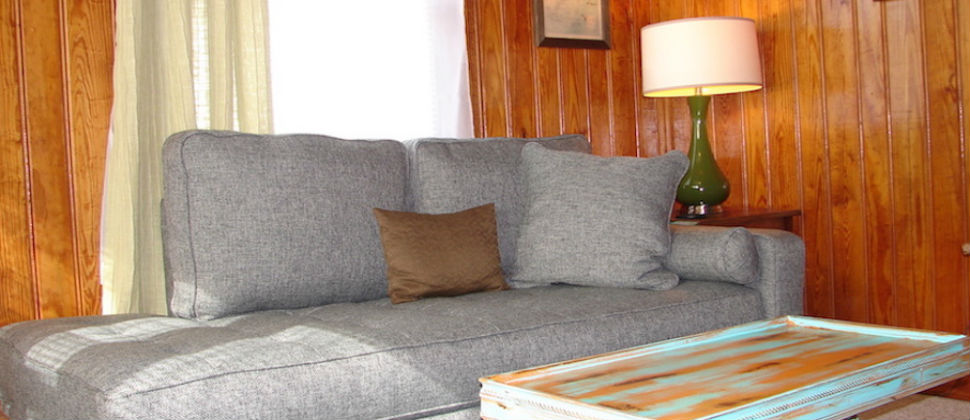 Seating area with grey chaise lounge sofa with natural light touching one end, green vintage lamp on end table.