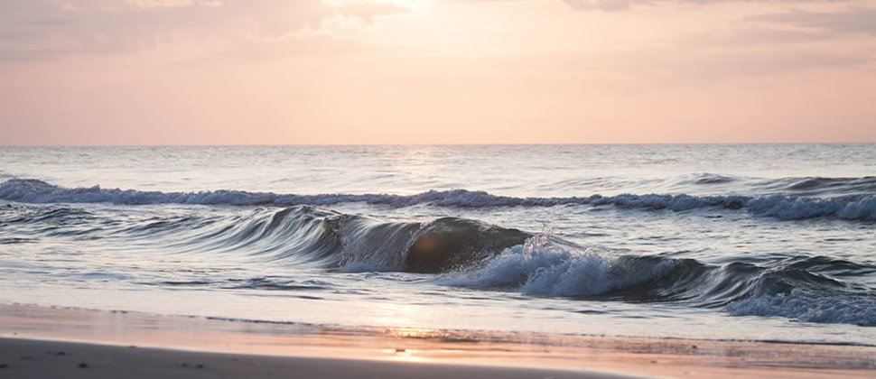beach at sunrise with crashing waves and orange color sky