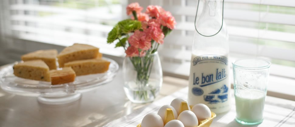 breakfast table with fresh ingredients including white eggs, bright yellow egg carrier, vintage milk canisters and homemade cornbread