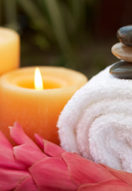 massage-therapy towel and candles with meditation stones and pink flower