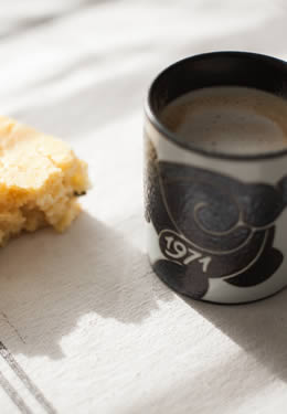 a piece of cornbread with a decorative black coffee cup dated from 1971