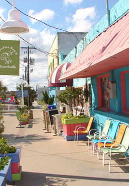 view of boardwalk with blue green and salmon flower boxes and chairs green flags flying