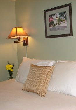 queen bed with a tan throw pillow in front of four white pillows.  Yellow flowers on the nightstand