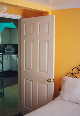 full bed with orange colored walls, a white open door showing the kitchen in the background