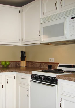 cottage one kitchen with dark countertops, white cabinets and a clear bowl displaying three green apples
