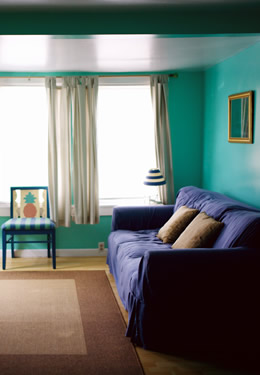cottage one living room with blue couch, striped blue and green chair with pineapple design on the back and tv