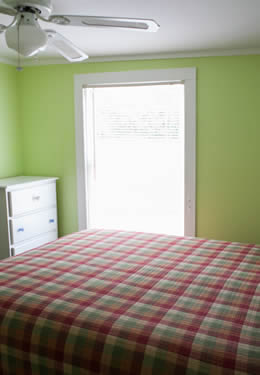 plaid blanket covering a queen size bed.  Lime green walls and a dark green curtain along the back wall