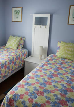 room with two twin bed, blue painted walls, window with white blinds and bamboo style laminate flooring