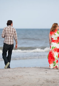 woman with flowing tropical dress and man with pant cuffs rolled seen from the back walking toward the blue ocean