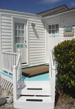 two white steps leading up to the aqua painted porch and front door of cottage
