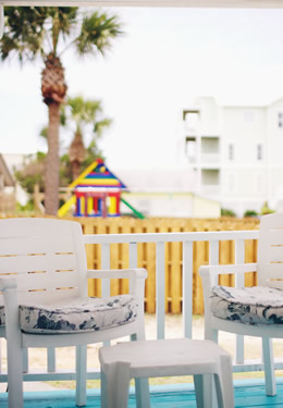two white patio chairs on the aqua painted porch of cottage 2 with a palm trees in the background