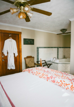 queen size bed with red and white duvet, white luxury robes hanging behind the door and whilrpool tub in background