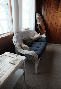 White wicker loveseat with a blue cusion against two windows with white drapes and antique mirror against the back wall