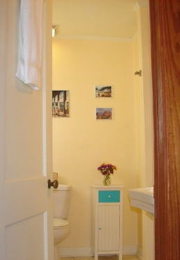 white bathroom door open with showing and a small dresser with a aqua blue drawer and blue knobs