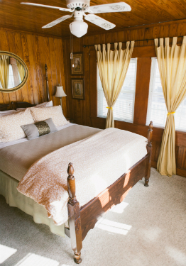 Queen bed with tan blanket and tan and white duvet. Two windows with yellow drapes and white blinds.