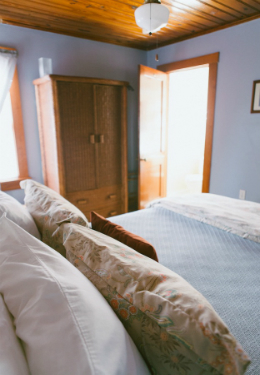 Queen bed with blue blanket and tan pillow shams. Brown wicker hutch in background with open door leading to bathroom.