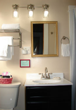 bathroom with brown vanity and off white counter top and chrome faucet. Wall mirror above the sink with overhead lights.