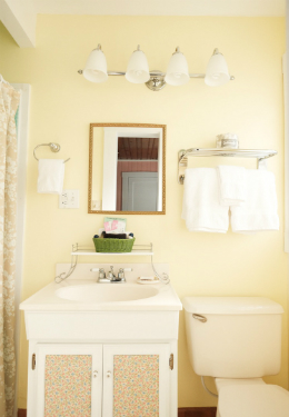 yellow painted bathroom with white luxury towels hanging on a rack and a green basket on a white vanity
