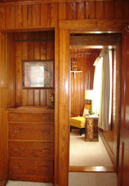 Honey stained knotty pine walls with built in dresser, peaking through to bedroom with yellow chair and green lamp.