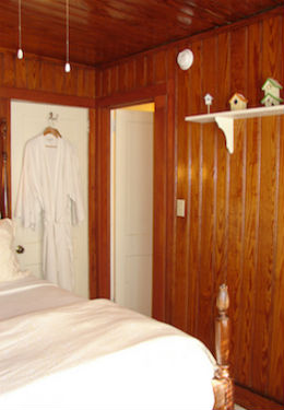 Bed with duvet folded at the end of the bed, white bathrobes hanging on the door, honey stained knotty pine walls.