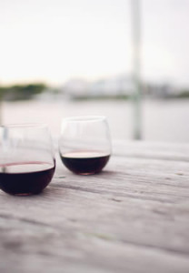red wine in two stemless glasses set on wooden pier with the sun setting on the canal in the background