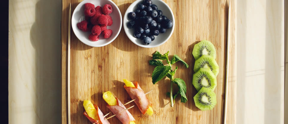 red raspberries, blueberries, pineapple wrapped in Canadian bacon and green parsley on wooden cutting board