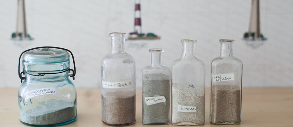 five old medicine bottles of sand from various beaches set on tan wooden table with lighthouse wallpaper in background