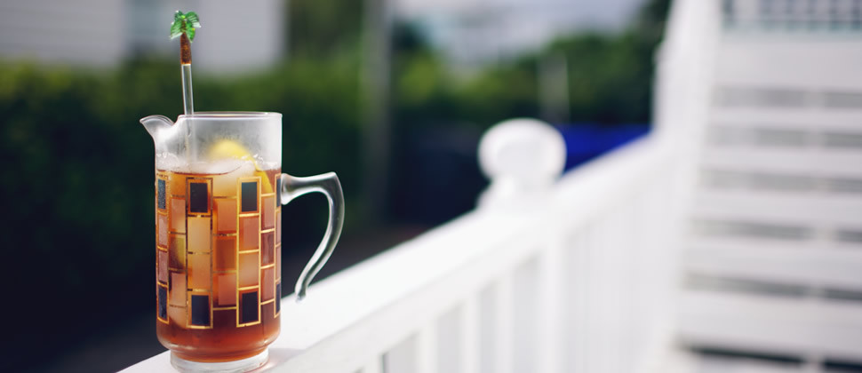 ice tea in clear glass decorated with black and gold piece of yellow lemon and palm tree stirrer sitting on white ledge of back deck
